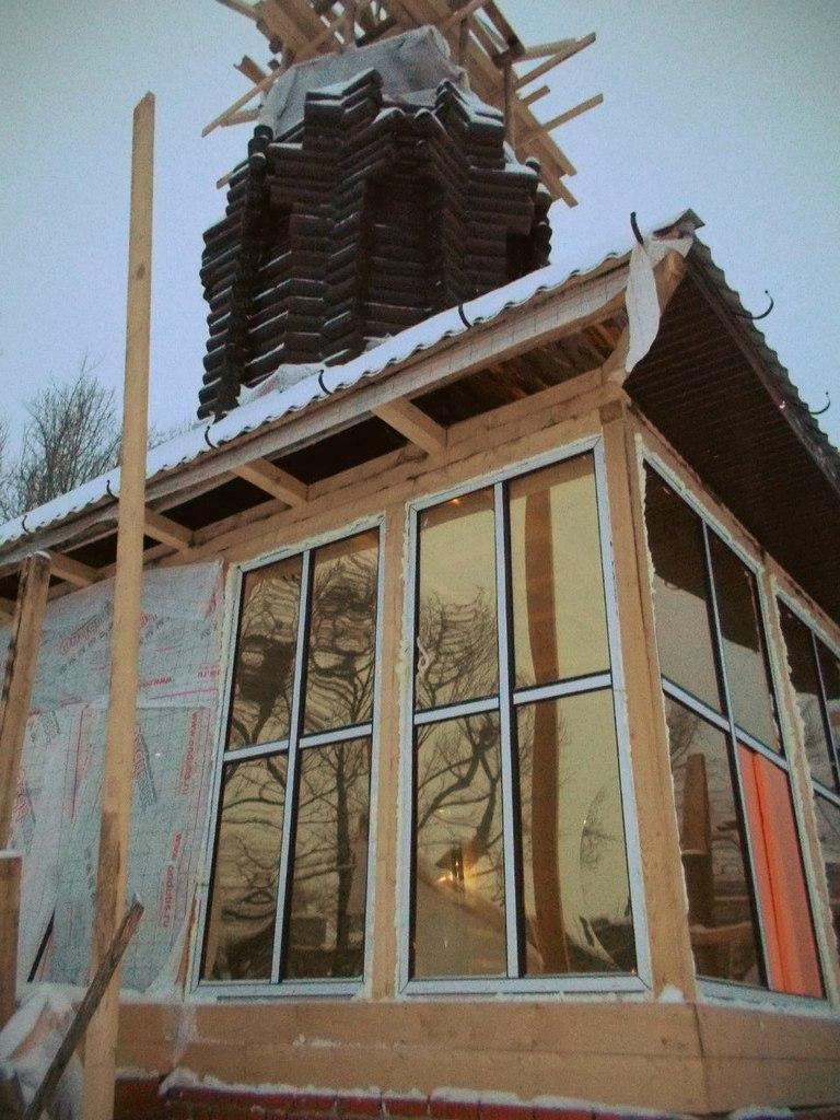 Над будущим свечным ларьком доделывают крышу